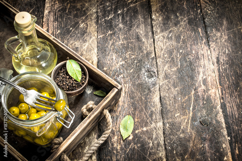 Foto Murales Pickled olives with oil and spices on an old tray.