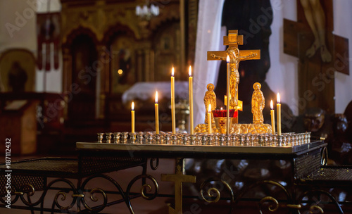 Candles burning on a candlestick in front of golden cross with Jesus - 187112432