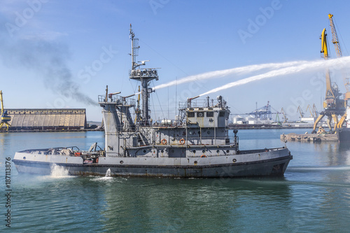 Fototapeta Navy firefighting ship in action. fire fighting a vessel in water from a ship.