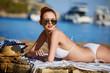Sexy beautiful woman in white bikini on Mediterranean sea coast