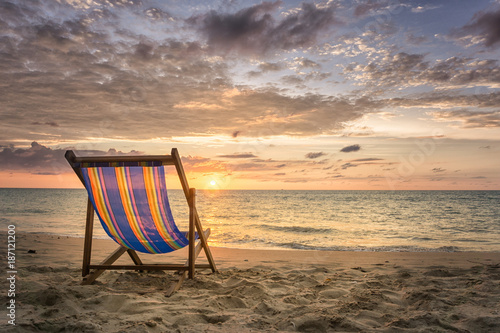 Empty beach chair at secluded beach during sunset - 187121200