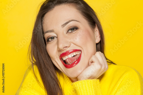 beautiful happy woman in a yellow sweater on a yellow background