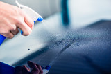 Close-up of hand spraying cleaning substance on the surface of a blue car at auto wash