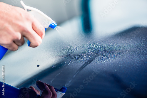 Close-up of hand spraying cleaning substance on the surface of a blue car at auto wash - 187133273