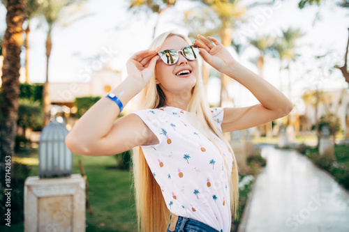 Tuinposter Spa Cheerful young woman in sunglasses in summer palms backgrounds