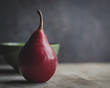 Red Pear in front of a green bowl with a dark background