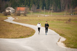 Young  veautiful couple runs on a path in park on autumn afternoon - 187147401