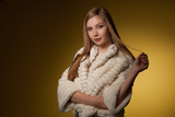 Beauty portrait of woman in fur winter jacket over yellow background - 187147889