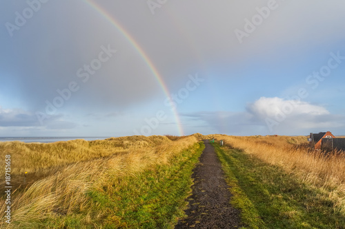 Fotobehang Noordzee Regenbogen über dem Deich