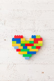 Top view on bright heart made of colorful plastic bricks on old wooden background or table. Creative building out of bright constructor bricks. Early learning. Developing toys - 187151892