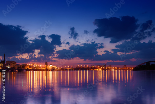 Fotobehang Kiev Havana bridge in Kiev at night with colorful illumination, beautiful clouds and reflection in Dnieper river. Wide angle