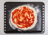 PIZZA RECIPE stage 4 - round ra pizza with tomato sauce on baking tray - 187155262