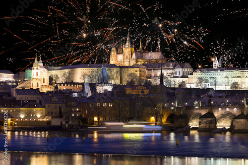 Fireworks above night colorful snowy Prague gothic Castle with Charles Bridge, Czech republic