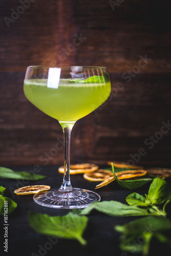 Foto Murales Green cocktail on the background of a wooden background.