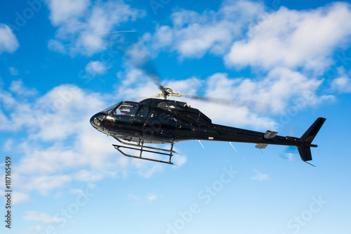 solo black helicopter in blue skies