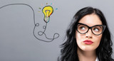 Light Bulb with young businesswoman in a thoughtful face