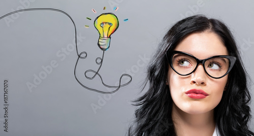 Light Bulb with young businesswoman in a thoughtful face - 187167070