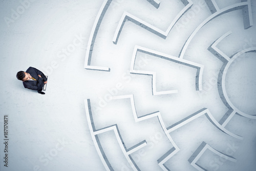Poster Hoogte schaal Business man looking at circular maze with nowhere to go