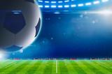 Big soccer ball above green stadium with bright spotlights - 187181417