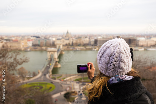 Foto op Plexiglas Cappuccino Young woman is taking a photo of Chain Bridge from top. Chain bridge is suspension bridge that spans the River Danube in Budapest, Hungary.
