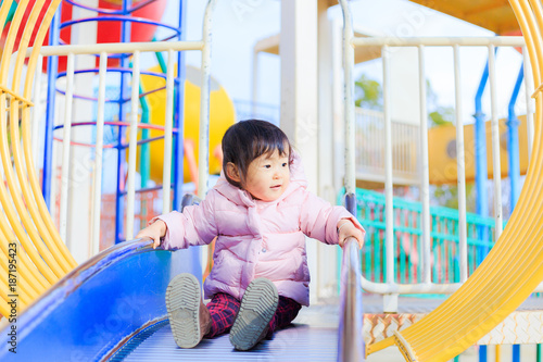 Foto Murales 公園の滑り台で遊ぶかわいい子供
