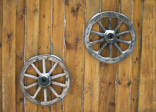 Two vintage wooden wagon wheel hanging on the wall