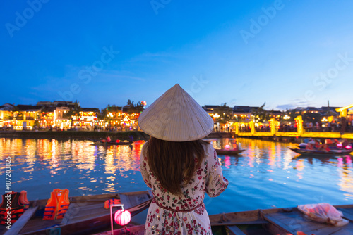 Foto Murales Woman tourist is sightseeing at Thu Bon riverside and wearing Non La (Vietnamese Hat) in Hoi An, Vietnam.