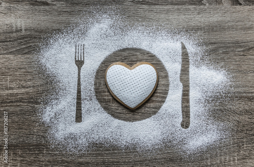 on a wooden background with powdered powder snow covered with a silhouette a plate a fork knife of appliances in the center lies a cookie in the form of a heart with white mastic  - 187206217