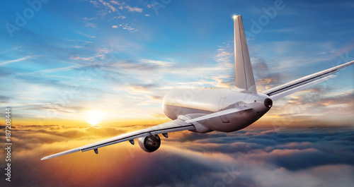 Commercial airplane jetliner flying above clouds in beautiful sunset light. - 187208444