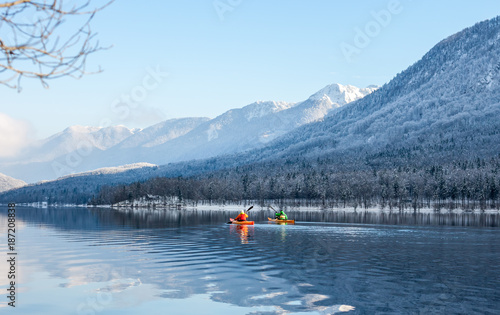 Foto Murales two people kayaking in the winter among mountains