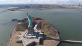Aerial shot of the gorgeous Statue of Liberty with big city in the background - 187218269