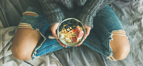 Healthy winter breakfast in bed. Woman in sweater and jeans holding rice coconut porridge with figs, berries, hazelnuts, top view, wide composition. Clean eating, vegetarian, comfort food concept - 187218222
