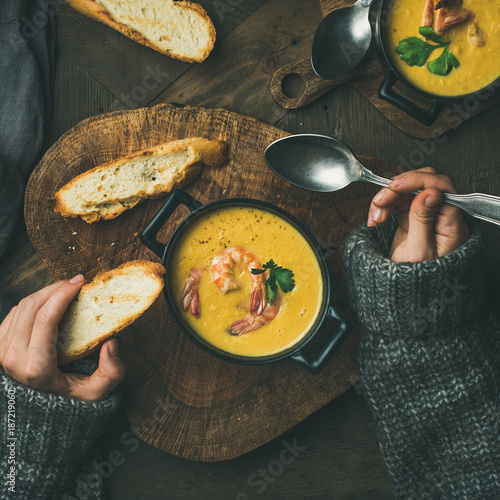 Woman in sweater eating corn creamy soup with shrimps in individual pot, top view, square crop. Woman' s hand with spoon and bread. Flat-lay of rustic table. Slow food, winter warming food concept - 187219060