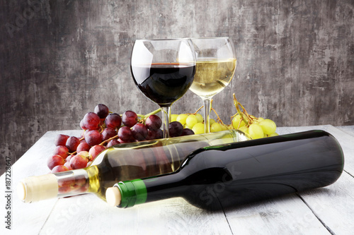 Foto Murales Glasses of wine and grapes on wooden background. red and white wine concept