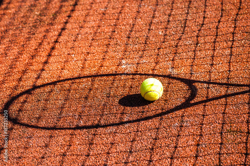 Fototapeta Shadow of a tennis racket and ball on court