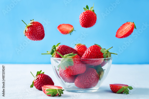 Foto Murales Fresh strawberries in a glass bowl with flying slices