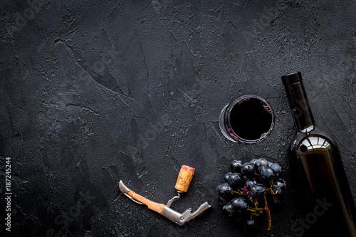 Open the wine. Corkscrew near bottle on black background top view copyspace