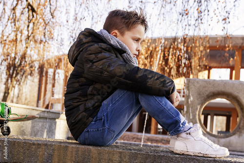 Elegant child relaxing sitting on a marble bench
