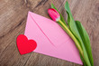 Envelope and tulip on a wooden table