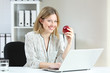 Businesswoman holding an apple looking at you at office