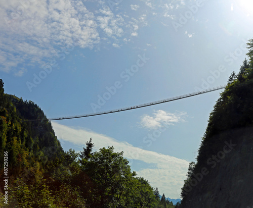 long suspension bridge between two mountains with many intrepid adventurers who pass through it