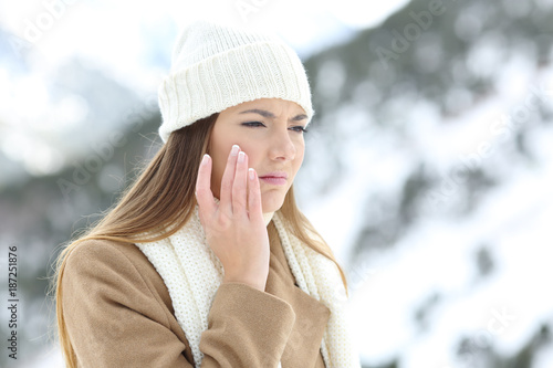 Foto Murales Angry woman using a sking protection cream in winter