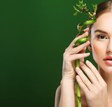 young beautiful woman with bamboo over green background