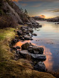Evening light, ocean, stones and rocks by the seaside, warm light and sunset in the background. - 187254016