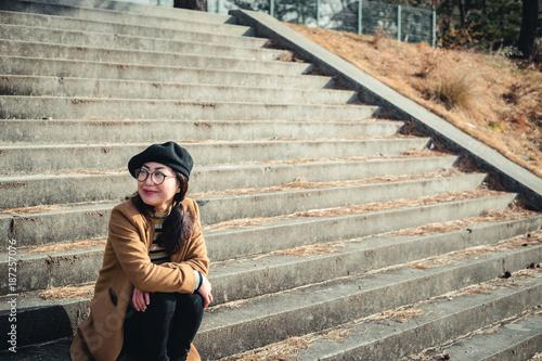 Foto Murales 河川敷の階段に座っている女性