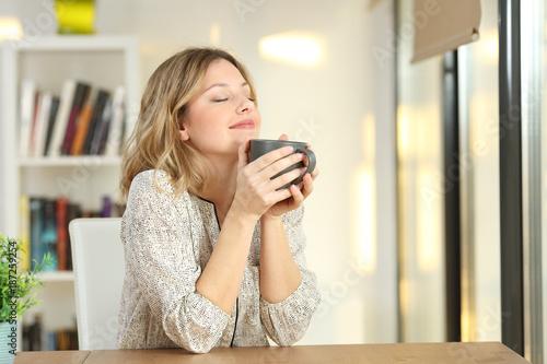 Leinwandbild Motiv Woman breathing holding a coffee mug at home