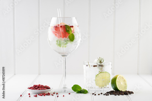 gin and tonic alcohol drink cocktail glass ice fruit garnish plain black white background - 187265899