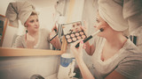 Woman in bathroom applying contour bronzer on brush - 187277057