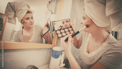Woman in bathroom applying contour bronzer on brush