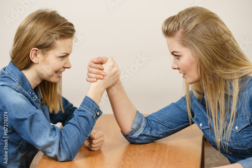 Two women having arm wrestling fight